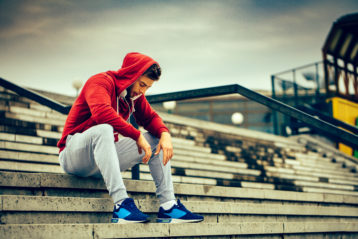 Young man resting on the stairs after running